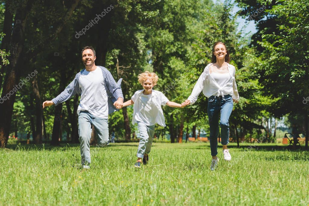happy family holding hands and running in park during daytime