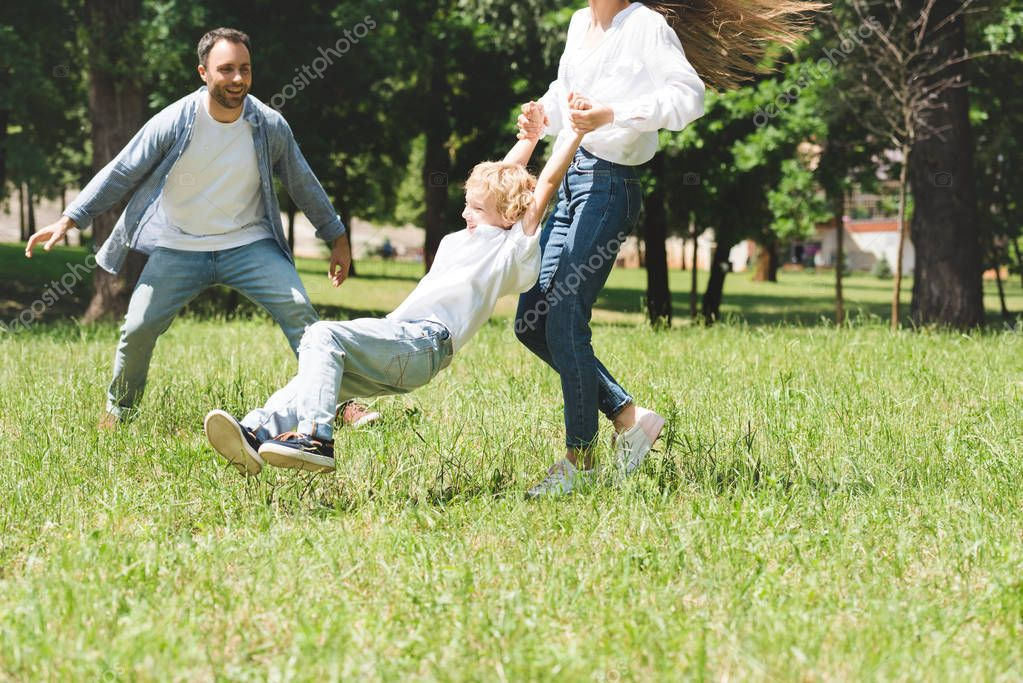 family spending time together, woman spinning son in park