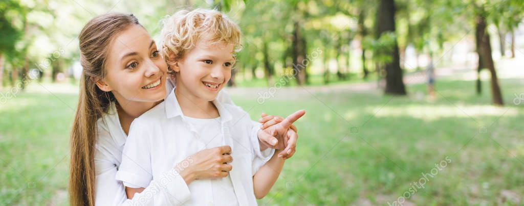 panoramic shot of beautiful mother hugging adorable son pointing with finger at copy space in park