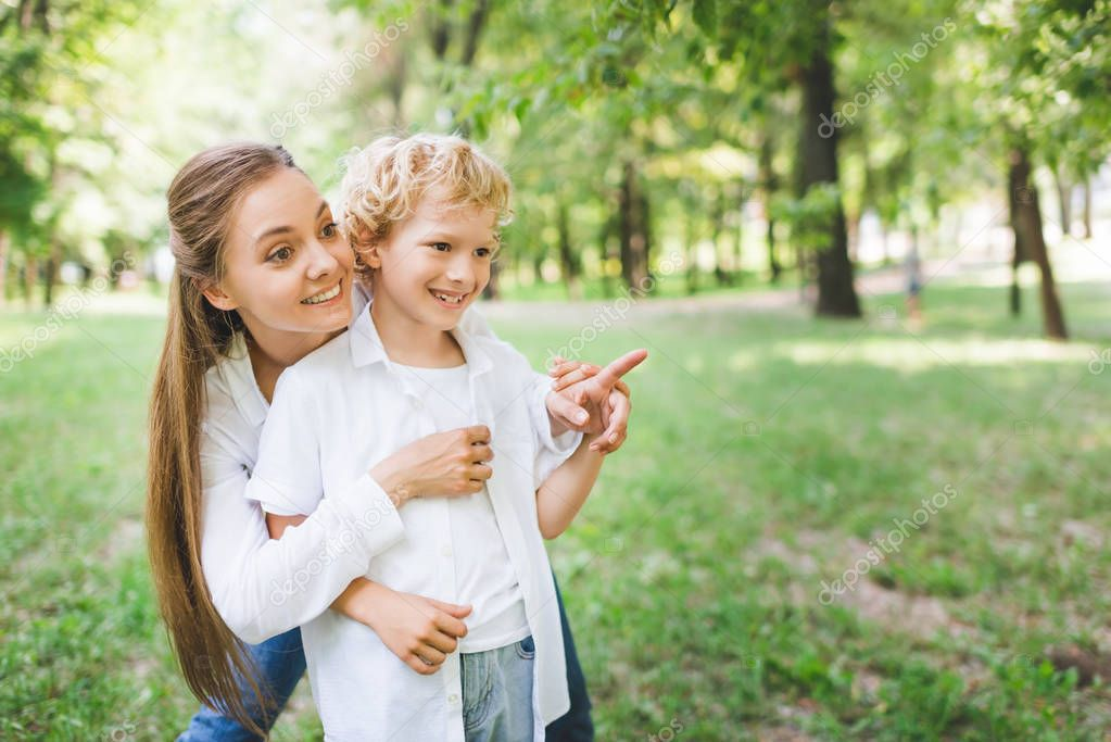 beautiful mother hugging adorable son pointing with finger at copy space in park