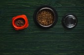 Schüsseln mit Tiernahrung in Reihe auf grüner Holzoberfläche