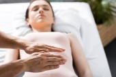 cropped view of healer standing near woman lying with closed eyes on massage table and holding hands above her body