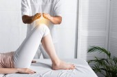 partial view of healer standing near woman on massage table and holding hands above her knees