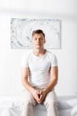 elülső kilátás az ember fehér póló ül a masszázságy csukott szemmel klinikán
