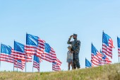 Photo selective focus of father in military uniform standing with cute kid near american flags