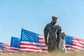 selektivní zaměření vojenského muže na čapku s pohledem na chlapce a americké vlajky
