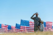 selective focus of patriotic man touching cap near kid and american flags