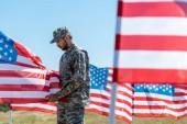 messa a fuoco selettivo delluomo in uniforme militare e tappo in piedi e toccando bandiera americana