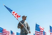 handsome soldier in military uniform and cap holding american flag while standing against blue sky