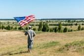 uomo militare in uniforme in piedi sullerba e tenendo bandiera americana