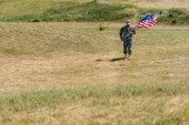 Photo selective focus of handsome soldier in uniform walking and holding american flag in summertime