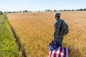 Photo handsome man in military uniform holding american flag while standing in field