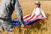 cropped view of man in military uniform holding american flag with cute daughter in field