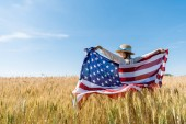Photo back view of kid in straw hat holding american flag in golden field