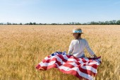 cute child in straw hat holding american flag in golden field with wheat