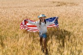 cute and happy child holding american flag in golden field