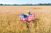 Photo back view of kid in straw hat holding american flag with stars and stripes in field with rye