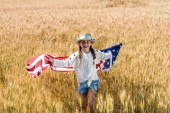 Photo cute and happy kid holding american flag with stars and stripes in golden field
