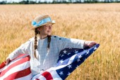 Photo cheerful kid holding american flag with stars and stripes in golden field