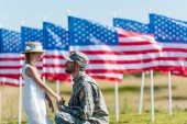 Photo happy military man looking at kid in straw hat while holding hands near american flags with stars and stripes