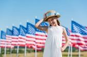 šťastné dítě stojící v bílých šatech a dotýkání se slaměný klobouk poblíž amerických vlajek