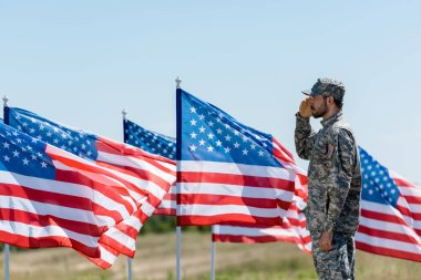 man in military uniform and cap standing and giving salute near american flags