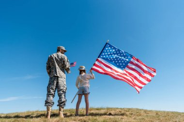 Soldier in military uniform standing near kid with american flag against blue sky stock vector