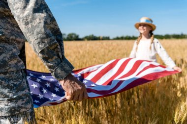 Cropped view of man in military uniform holding american flag with daughter in field stock vector
