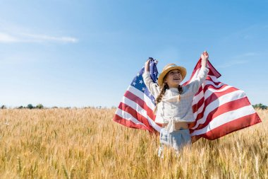 cheerful child in straw hat holding american flag in golden field