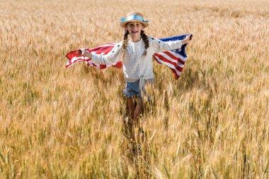happy kid in straw hat holding american flag in golden field