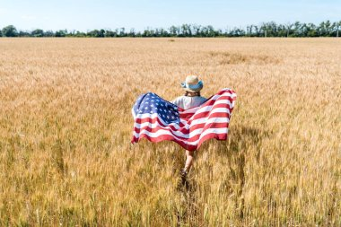 Back view of kid in straw hat holding american flag with stars and stripes in field with rye stock vector
