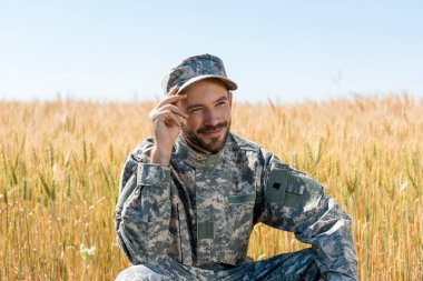 Positive military man touching cap and smiling in field stock vector