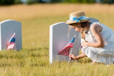 selective focus of adorable kid in straw hat sitting near headstone with american flag in graveyard
