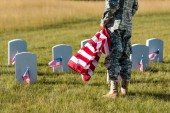 cropped view of man in military uniform holding american flag while standing in graveyard