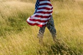 Photo cropped view of man in camouflage uniform holding american flag in field