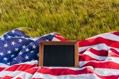 blank chalkboard on american flag with stars and stripes on green grass