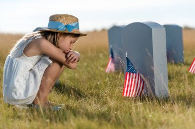 sad kid in straw hat sitting near headstones with american flags