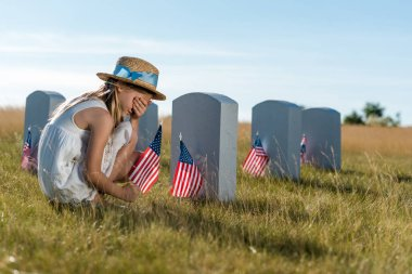 kid in straw hat covering face while sitting near headstones with american flags