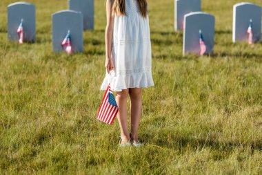 Cropped view of kid in white dress standing on graveyard with american flag stock vector