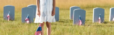 panoramic shot of kid in white dress standing on graveyard with american flag