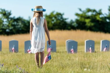 back view of kid in white dress standing on graveyard with american flag