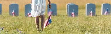 Panoramic shot of child in white dress standing on graveyard with american flag stock vector