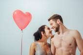 nejeden pár se usmívá a dívá se na sebe, zatímco dívka držící červený balónek