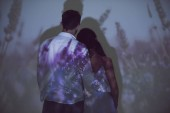 back view of girl and man hugging while standing in darkness on light of projector