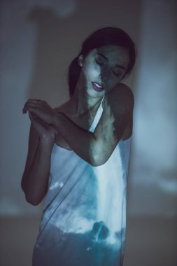 beautiful girl standing in darkness with closed eyes in pose