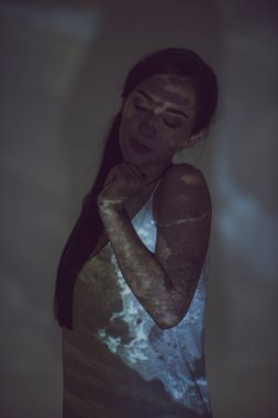 beautiful woman standing in darkness with closed eyes and hand near chin