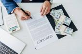 pohled na podnikatele, který drží pero blízko smlouvy a peníze v kanceláři