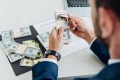 selektivní zaměření obchodníka, který drží dolarové bankovky poblíž smlouvy v úřadu