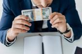 oříznutý pohled člověka páchnoucích dolarových bankovek v blízkosti notebooku a pera