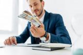 selektivní zaměření peněz v rukou šťastného obchodníka